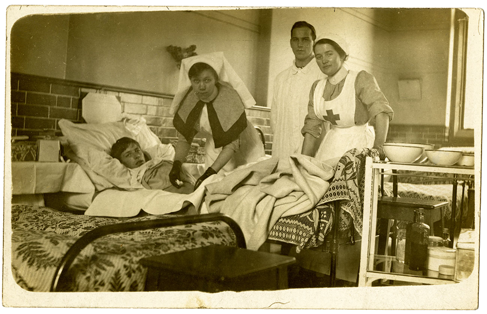 Postcard of nurses tending to a wounded soldier at the First Northern Hospital